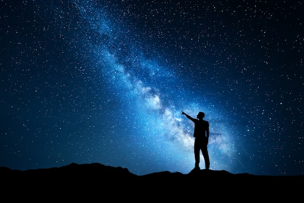 Silhouette of a standing young man pointing finger in night starry sky on the background of blue milky way.