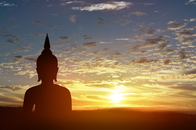 Silhouette statue of buddha at sunset background