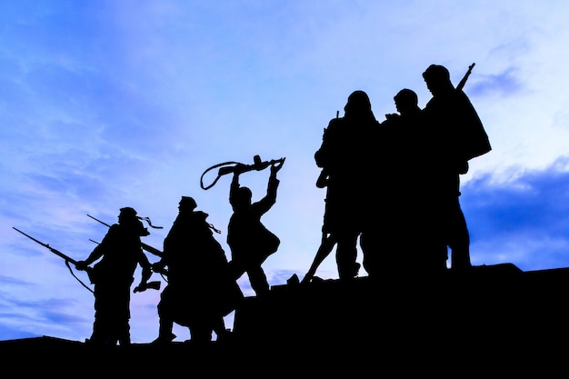 Silhouette of statue soldiers marching to war at the monument to the heroic defenders.