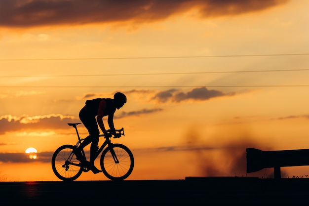Silhouette of strong male athlete riding bike in half bent position for higher speed on road
