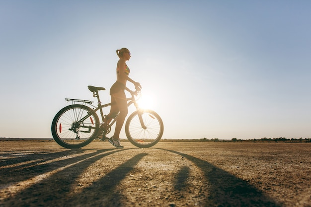 La silhouette di una donna forte in un abito colorato che siede su una bicicletta in una zona desertica. concetto di forma fisica.
