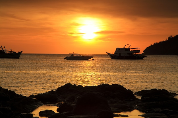 Silhouette sunset seascape of natural stone arch and toursit boats in andaman ocean