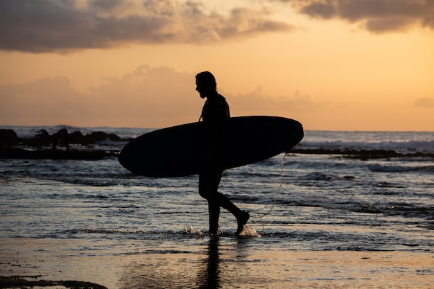 Silhouette of a surfer coming out of the water during sunset with his surfboard