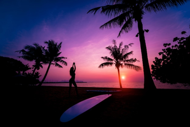 Silhouette of surfer girl with long surf board at sunset on tropical beach