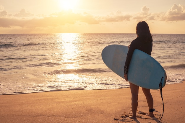 Silhouette of surfer woman carrying their surfboards on sunset beach with sun light