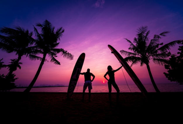 Silhouette of surfers couple holding long surf boards at sunset