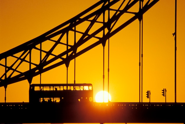 Silhouette of suspension bridge and double decker bus with sunset in background