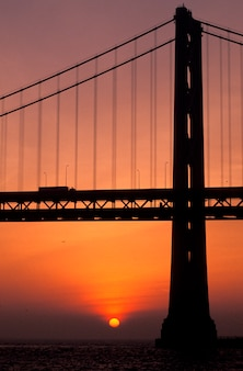 Silhouette of suspension bridge with orange sunset in background