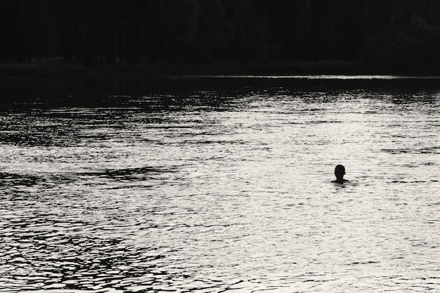 Silhouette of swimming man in center of river on forest background. sunlight reflected on water in grayscale. shiny water in river. monochrome amazing atmospheric landscape. minimalist scene.