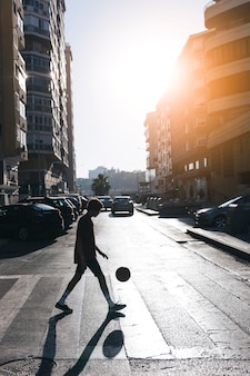 Silhouette of a teenage boy playing basketball on street in city