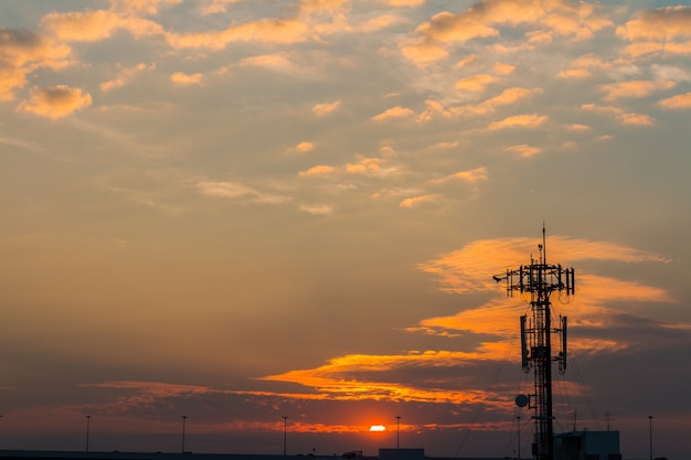 Silhouette telecommunication tower on sunset  background