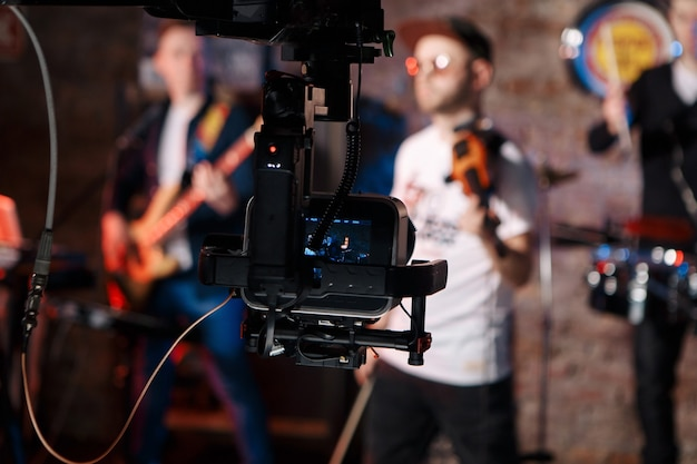 Silhouette of television camera hanging on crane working on stage and blurry concert background