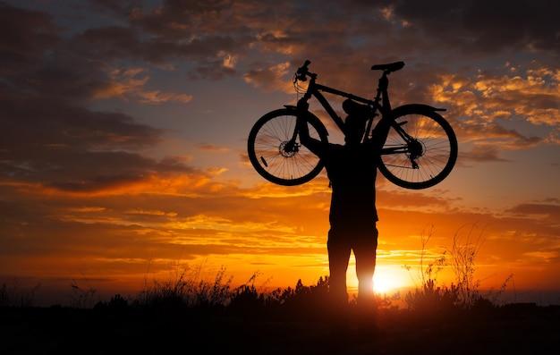 Силуэт человека стоит в действии, поднимая велосипед над головой на лугу с закатом