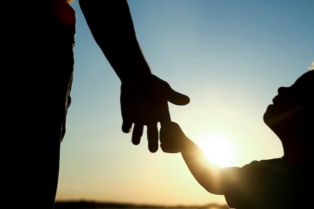 Силуэт родитель держит за руку маленького ребенка
