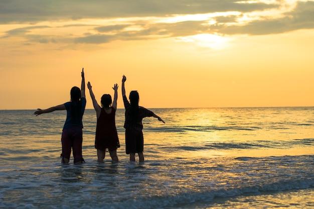 Силуэт три девушки счастливы на море и закат
