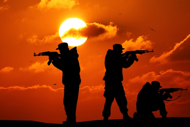 Silhouette of three soldier with weapons at sunset