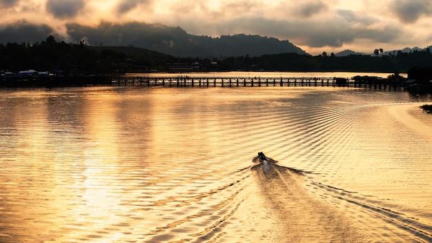 Силуэт туристической лодки плывет к деревянному мосту мон на рассвете на реке сонгкалия