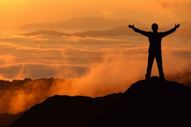 Silhouette tourist man spread hand on top mountain.