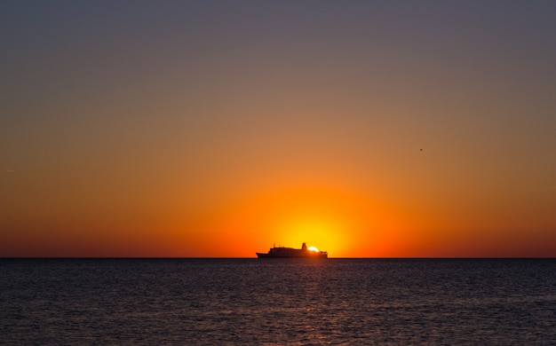 Silhouette of a tourist ship at sunset