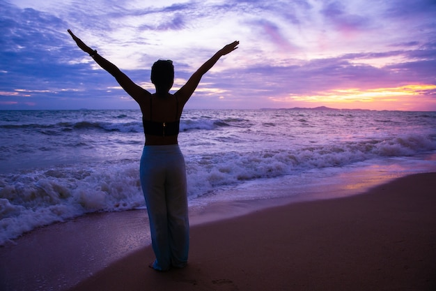 Silhouette tourist woman stretch hand relaxing on the beach in sunset or sunrise with twilight sky