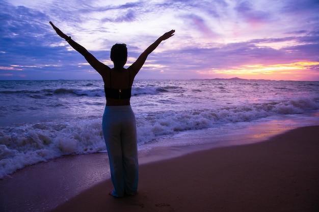 夕暮れや日の出、夕暮れの空でビーチでリラックスしたシルエットの観光客の女性のストレッチ手