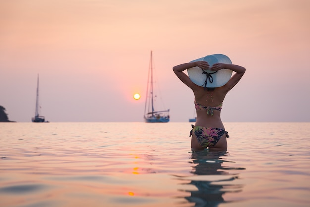 Silhouette of traveler asian woman with bikini relaxing on sea beach at sunset in koh kood, thailand