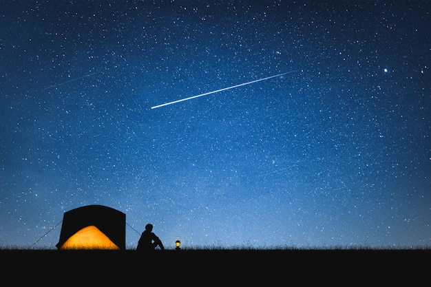 Silhouette of traveler camping on the mountain and night sky with stars. space background.