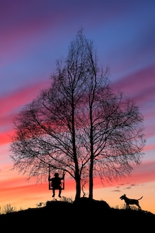 The silhouette of the tree in the form of a heart, with a swing with a child and a dog at sunset. high quality photo