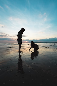 Silhouette of two asian child girls playing on the beach together at the sunset time with beautiful sea and sky. family enjoy with nature concept.