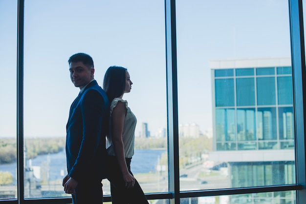 Silhouette of two business people leaning against each other