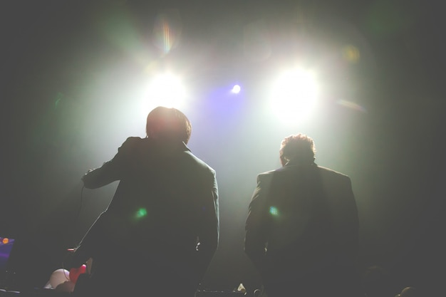 Silhouette of two dj performing at a concert