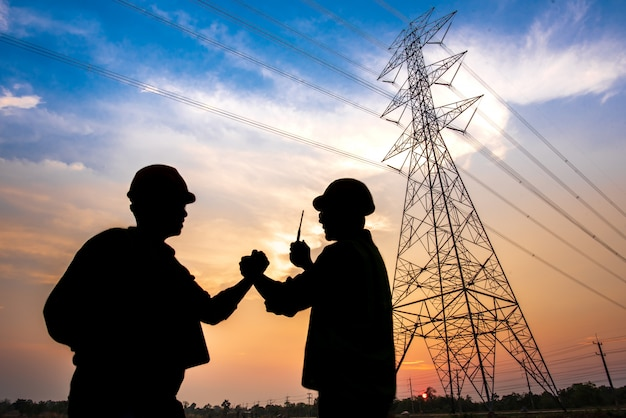 Silhouette of two electrical engineers standing at a power station standing in the air shaking hands agreeing to the production of electric power.