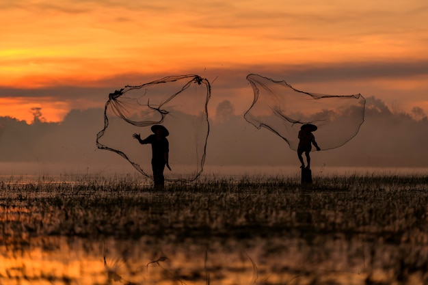 Silhouette of two fisherman  fishing with a net at sunset.