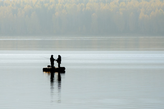 Silhouette of two fishermen in a boat