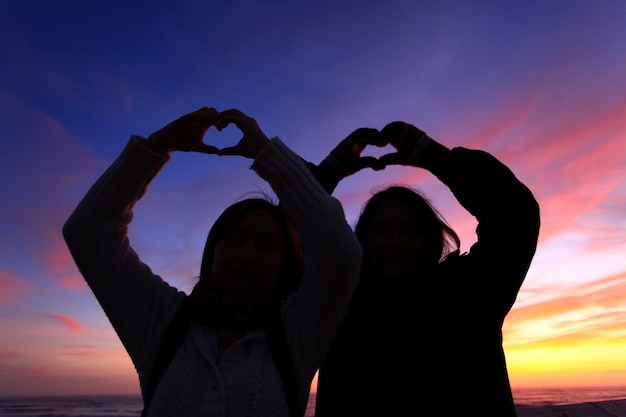 Silhouette of two grils forming thier hand to heart shape