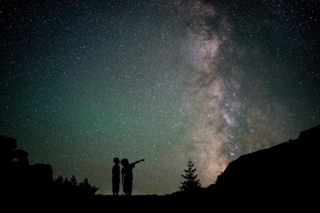 シルエット2人の小さな男の子、銀河系と美しい夜空、星空を背景に Premium写真