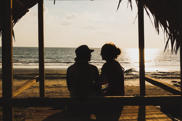 Silhouette two lovers sitting on the hut