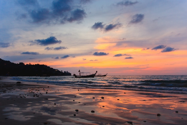 Silhouette of two traditional longtail boats at low tide at sunset on the kamala beach in thailand.
