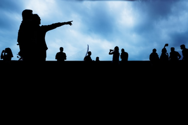 Silhouette of unrecognizable people pointing with a dark background.