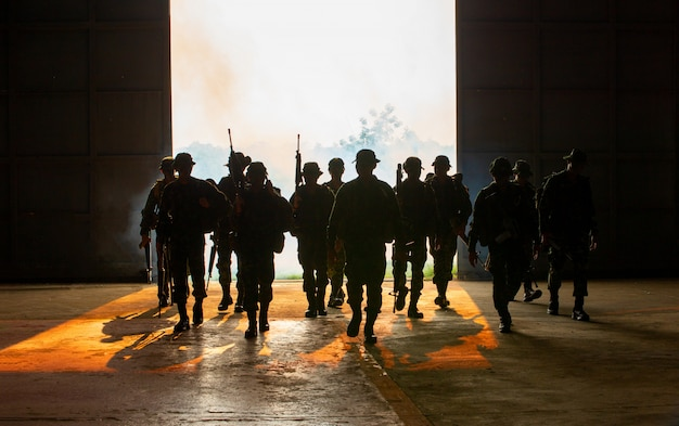 Silhouette of unrecognized soldiers with rifle walk through smoke