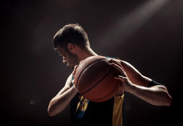 Profili il punto di vista di una palla del canestro della tenuta del giocatore di pallacanestro su spazio nero