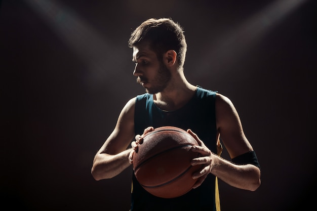 Silhouette view of a basketball player holding basket ball on black