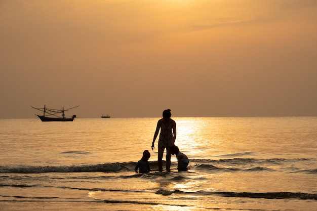 Silhouette view of family take a vacation in the summer time with sea scape