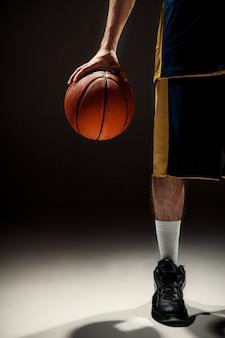 검은 배경에 바구니 공을 들고 농구 선수의 실루엣보기