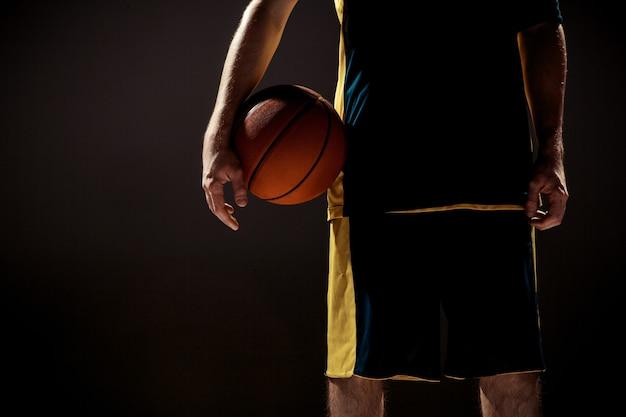 검은 벽에 바구니 공을 들고 농구 선수의 실루엣보기