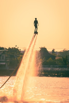 Silhouette and vintage color styl  of showing flyboard on chaophya river during chinese new year celebrations