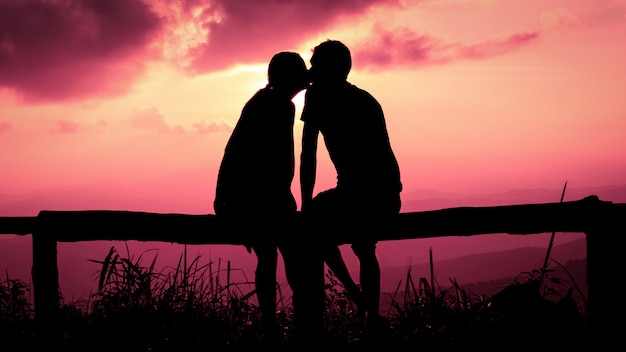 Silhouette of wedding couple in love kissing and holding hand together during sunset with pink sunset sky