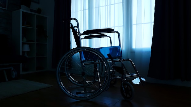 Silhouette of wheelchair next to a big window in empty room