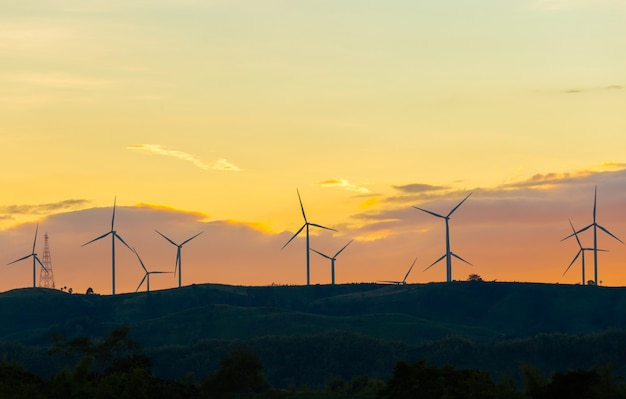 Silhouette of wind turbines at sunset in evening time, alternative energy