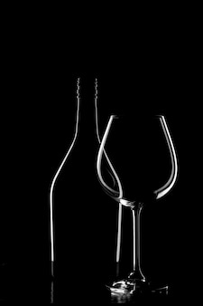 Silhouette of a wine bottle and wine glass on black background